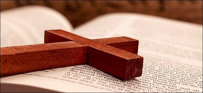 Photograph of a wooden cross on the pages of an open Bible