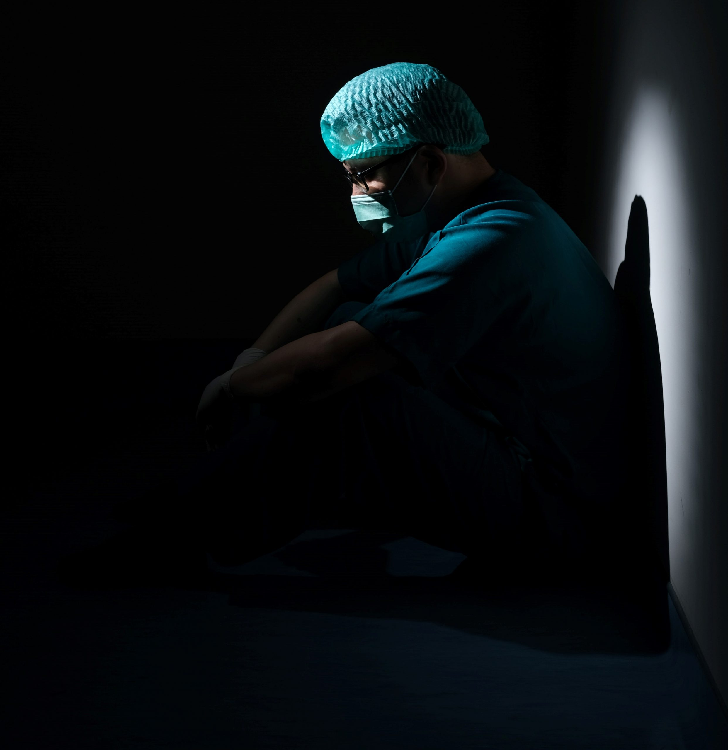 A photo of a surgeon in the shadows looking forlorn