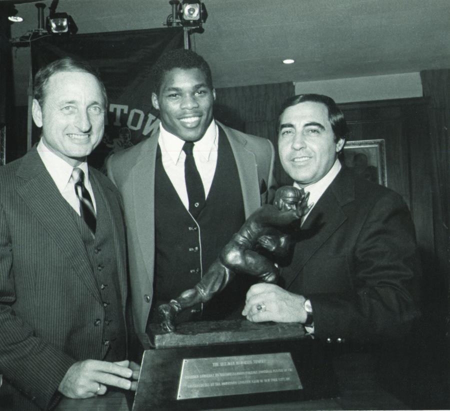 Vince Dooley with Herschel Walker poising with the Heisman Trophy, 1982.