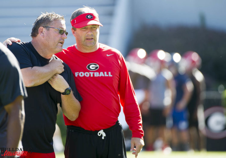 Offensive line coach Sam Pittman and Kirby Smart appear to be discussing it player as they watch a drill