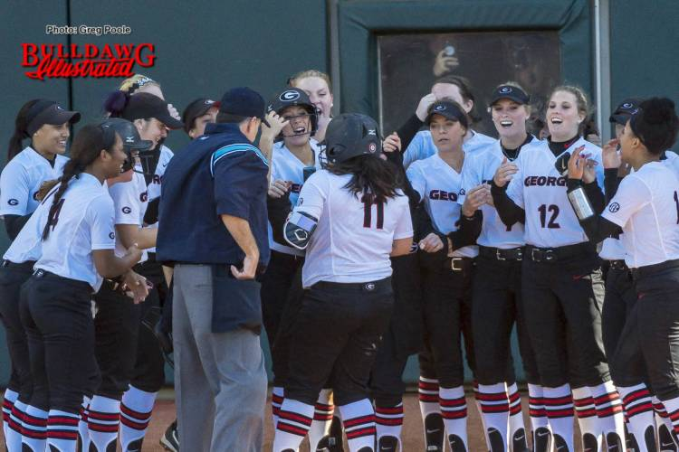 Mahlena O'Neal greeted by her teammates at home plate after her home run