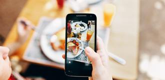 Person holding phone taking picture of served food 693267 listing