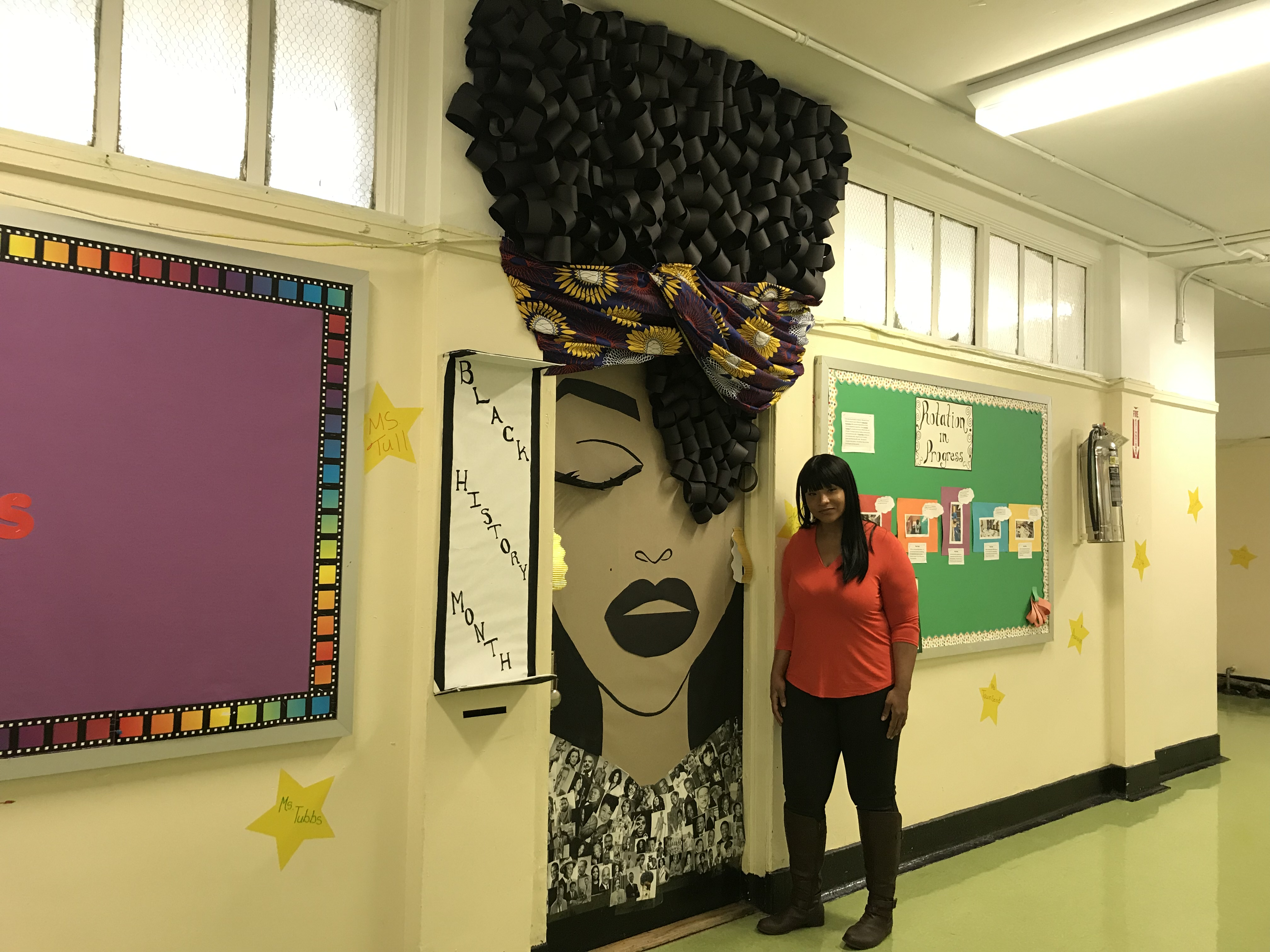 Hollie Tubbs standing next to her Door Art at PS 231 at 54 in Bedford Stuyvesant. The assistant teacher wanted to create an inspiring piece for Black History Month. (Photo credit: Kadia Goba/Bklyner)