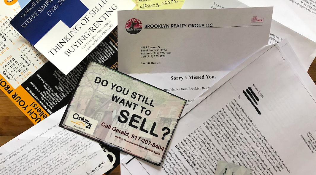 Here are some of the letters and postcards some members throughout Community Board 17 received from developers asking to buy their homes. (Photo credit: Allyson Martinez)