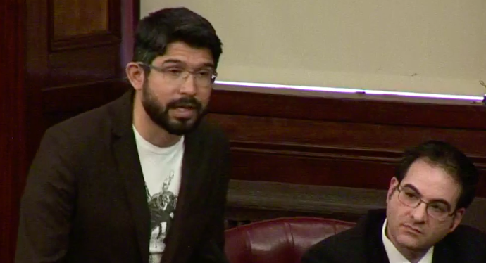Councilman Carlos Menchaca explaining his vote to oust Councilman Kalman Yeger as the Boro Park lawmaker looks on. (Screenshot: City Council hearing video)