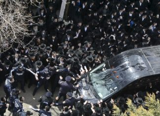 Cops struggle to control funeral-goers during the procession of Funeral procession of The Skulener Rebbe, Rabbi Yisroel Avrohom Portugal (Photo: Todd Maisel)