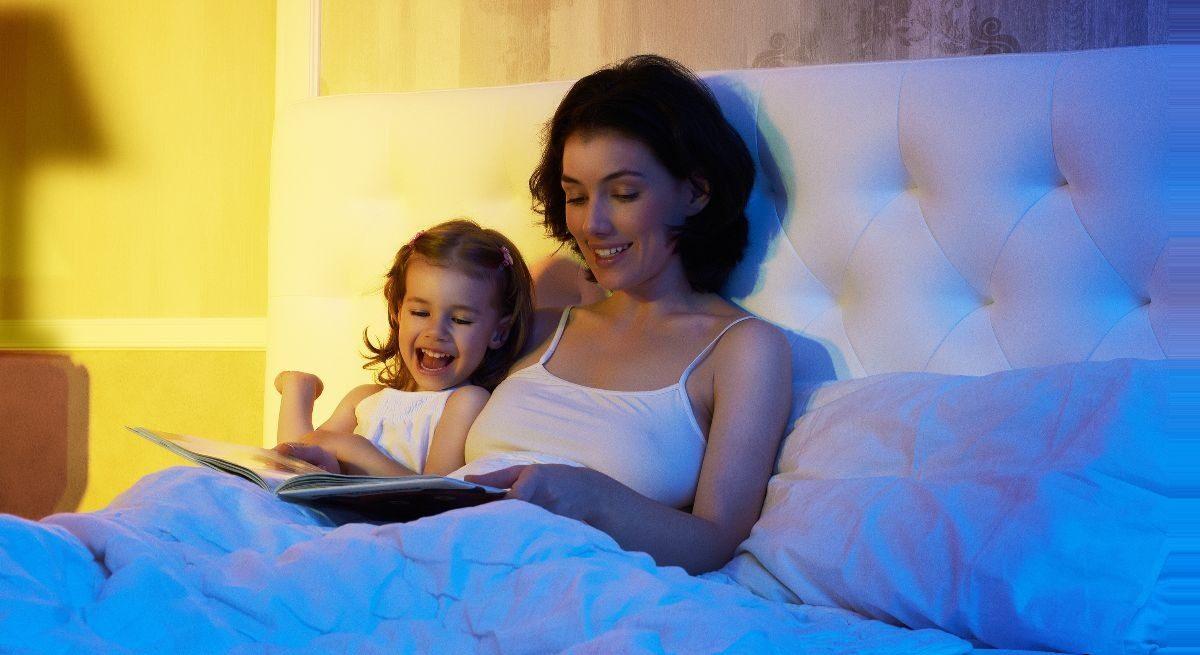 mae le historia para a filha na cama antes de dormir