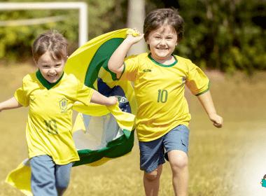 meninos correm com camisa oficial da seleção brasileira de futebol e bandeira do brasil