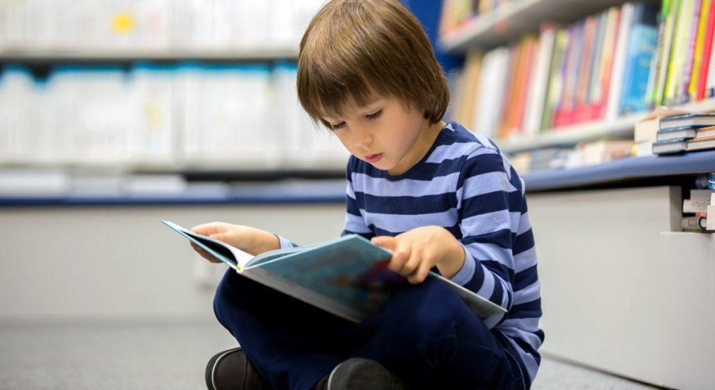 menino lendo livro em biblioteca