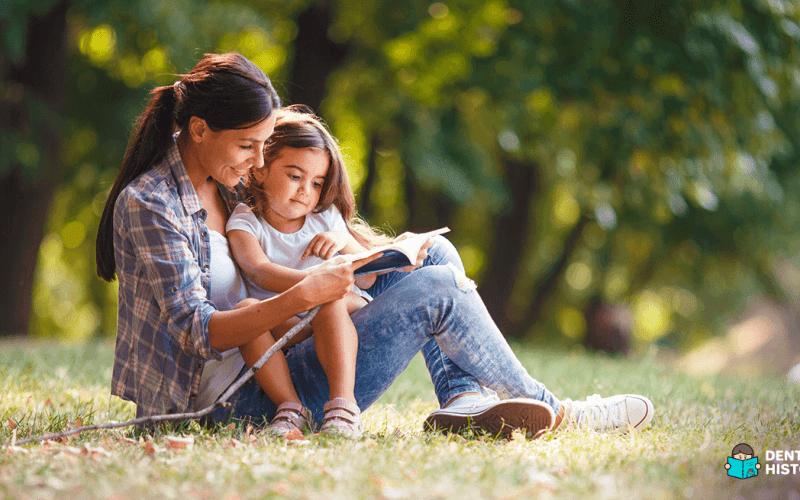 Mãe praticando leitura com a filha pequena