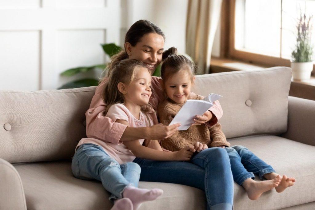 Mãe com filhas fazendo leitura em voz alta