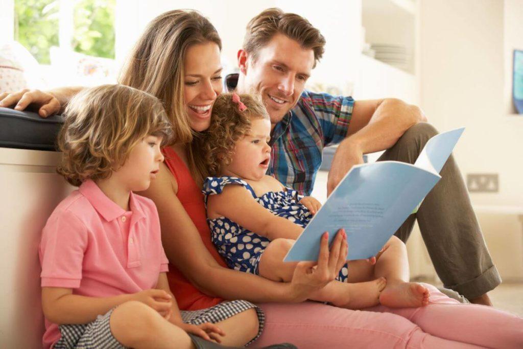 Família lendo para criança de 3 e 5 anos
