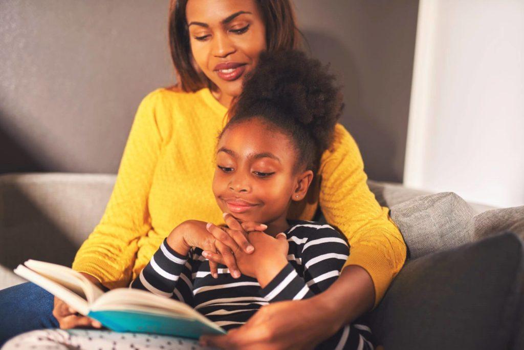 Mãe lendo para criança de 7 anos