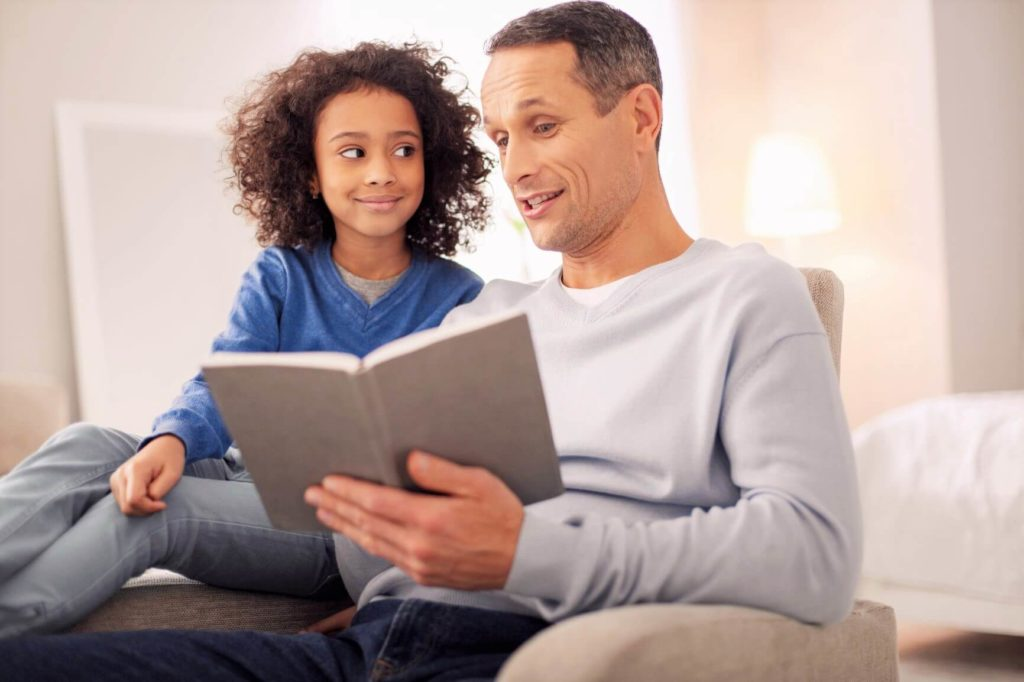 Pai lendo para criança de 10 anos