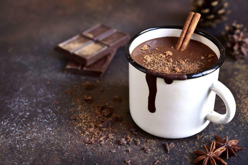 Caneca branca com chocolate quente e raspas de chocolate para decorar