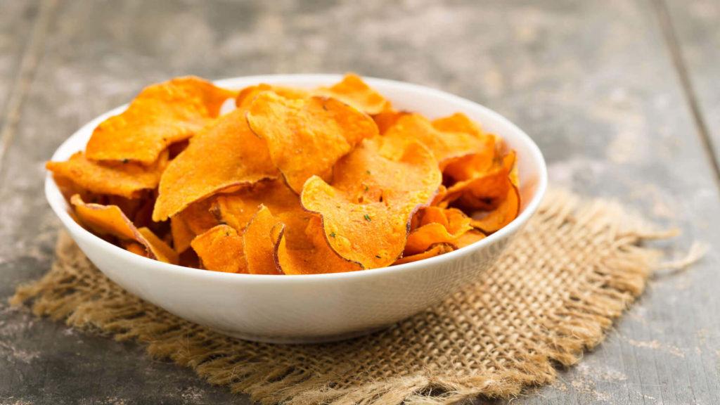 Chips de batata doce assada colocados em uma pequena vasilha branca