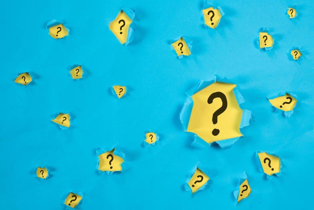 Imagem com fundo azul e diversos pontos de interrogação em amarelo