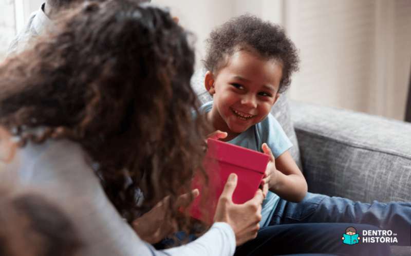 Criança negra sorrindo enquanto recebe uma caixa de presente dos pais.