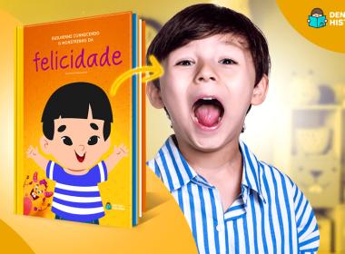 Menino branco sorrindo ao lado do livro Conhecendo o Monstrinho da Felicidade