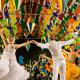 Mulher e homem vestidos de branco dançando em um ambiente decorado por bandeirinhas coloridas.