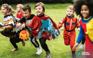 Crianças fantasiadas para o Halloween correndo em um gramado