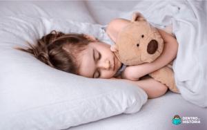 Menina loira dormindo com seu ursinho de pelúcia