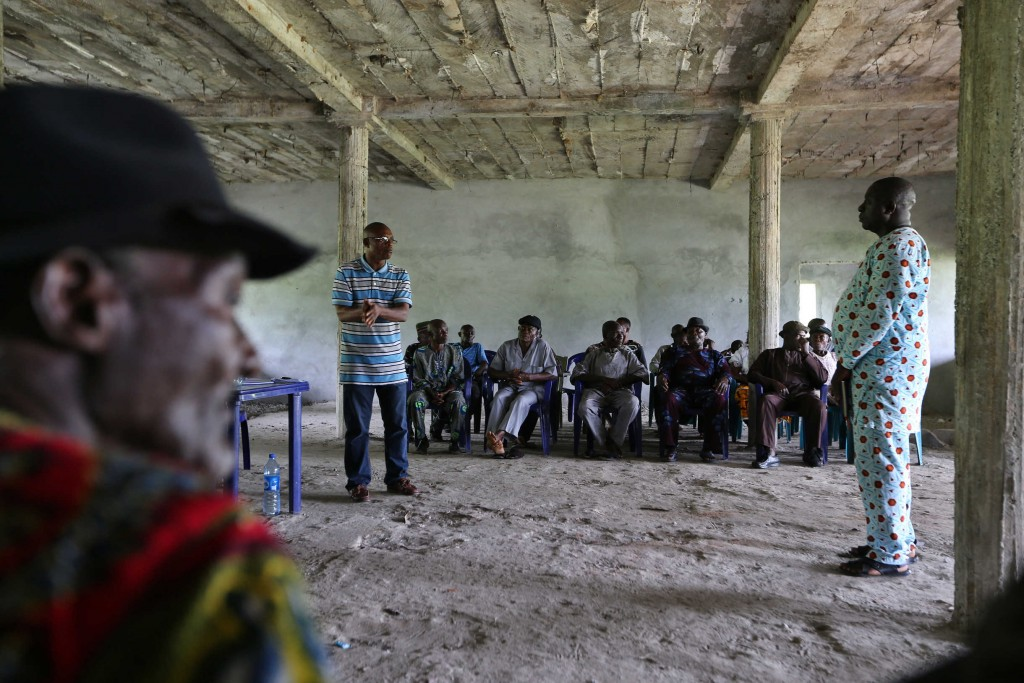 Elders meet in a partially reconstructed community center in Rumuekpe. Community members and their leaders are working hard to unify and find resources to rebuild following years of conflict, and say more access to revenues from oil produced and piped through their community could help them rebuild. Photo: George Osodi / Panos for Oxfam America.