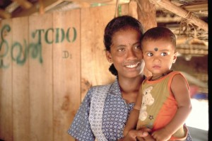 In Thiraimadu camp, Sri Lanka,Yealini, holds her one-month-old year old baby, Rohith. They stand outside their post-tsunami transitional shelter. Photo by: Howard Davies/Oxfam.