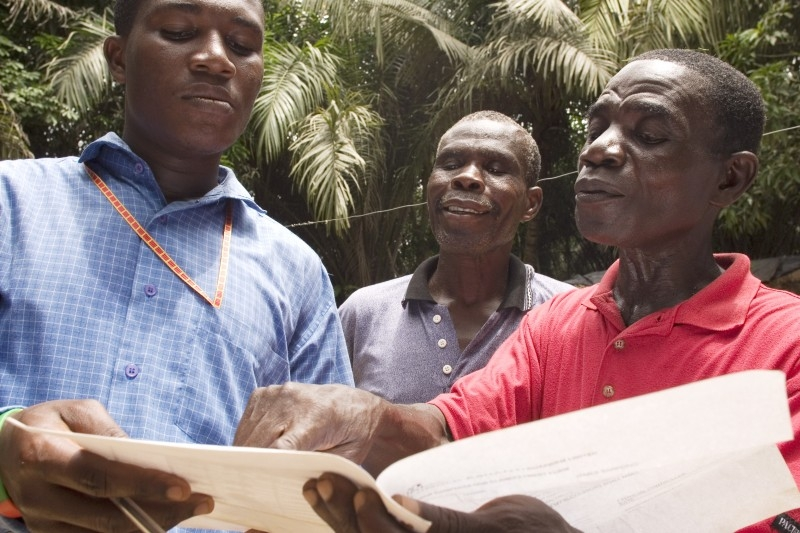 James Sarpong (right) showing an offer of compensation to visitors. Photo by Jane Hahn/Oxfam America