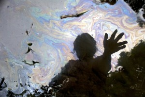 Cancer survivor Maria Garofalo reflected in the stream behind her home in the Ecuadorean Amazon. From the film Crude, directed and produced by Joe Berlinger. Photo Credit: Juan Diego Pérez.