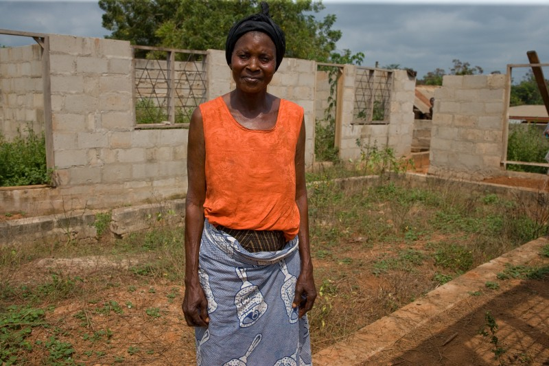 Theresa Yaa Serwaah walks inside the perimeter of her latest project in Mehame, Ghana, the third home she is building for her family of 13. A gold mine wants to move into the area. Photo by Neil Brander.