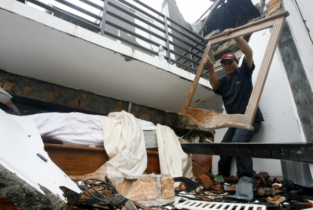 A resident searches for victims under a collapsed hotel in Padang on Indonesia's Sumatra island. Photo by Reuters/Crack Palinggi, courtesy of www.alertnet.org