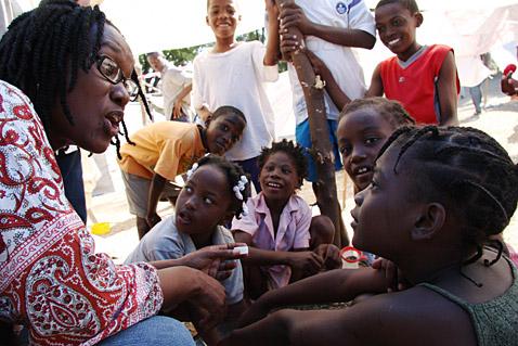 Oxfam's Yolette Etienne talks with quake survivors in Port-au-Prince. Photo: Liz Lucas / Oxfam America