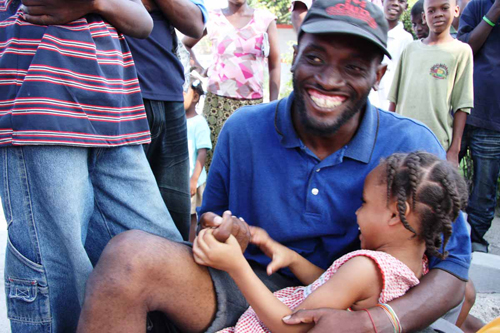 """Andy Charles Etienne and his daughter Christina, five. They escaped their collapsed home, and Etienne says """"we are alive and standing and give thanks for this."""" Photo by Liz Lucas."""
