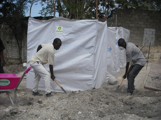 Residents help Oxfam dig latrines in a camp where tens of thousands of homeless people are now living.