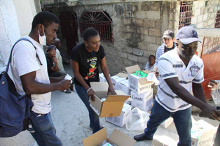 Stephan Durogene, left, helps distribute goods at a camp at Delmas 62. Photo by Kenny Rae/Oxfam America