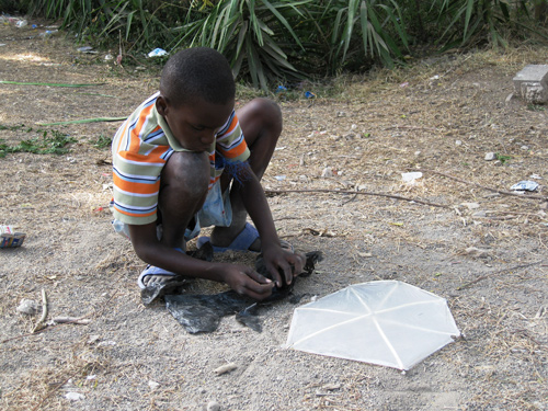 A boy assembles a kite at the Petionville Club, a golf course in Port-au-Prince that now houses thousands of displaced earthquake survivors. Photo: Liz Lucas / Oxfam America