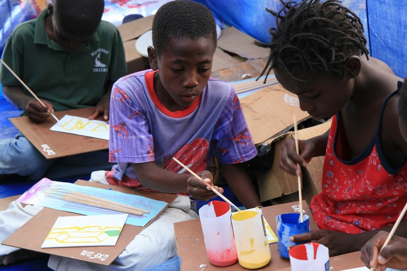 Chewthson Jean Baptiste and Ange Laure Bertrand create their paintings. Photo: Jane Beesley / Oxfam