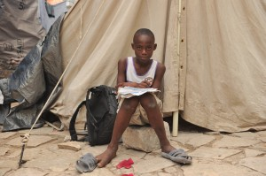 A boy does his homework in a camp for displaced people in Port-au-Prince, Haiti. Photo by Ami Vitale/Oxfam America