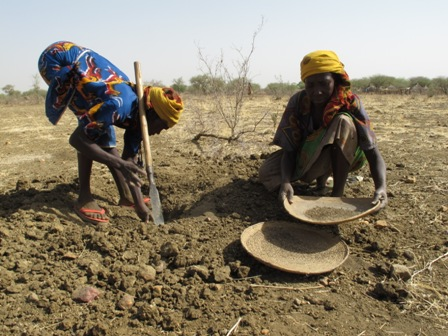 Women dig through anthills in search of small amounts of grain the insects have stored there. Photo by Oxfam