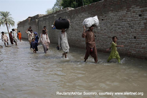 On August 10, a family wades through water while fleeing the flooded village of Karam Pur, 43 miles from Sukkur in Pakistan's Sindh province. Around 3,000 people displaced by the floods have now taken refuge in Sukkur.