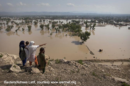 A person points towards their flooded home from a hilltop overlooking Nowshera, located in Pakistan's northwest Khyber-Pakhtunkhwa Province.