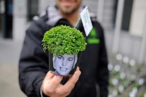 An Oxfam activist in Belgium holds a plant pot bearing a photo of Flemish Environment Minister, Joke Schauvliege. Photo credit: Tineke D'haese / Oxfam