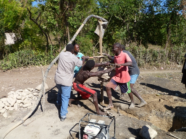 Men use a hand auger to drill a well in Haiti. Photo by Tom Mahin/Oxfam