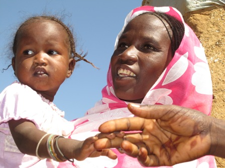 Maryam Gado's daughter holds the hand of a public health promoter. Photo by Elizabeth Stevens/Oxfam.