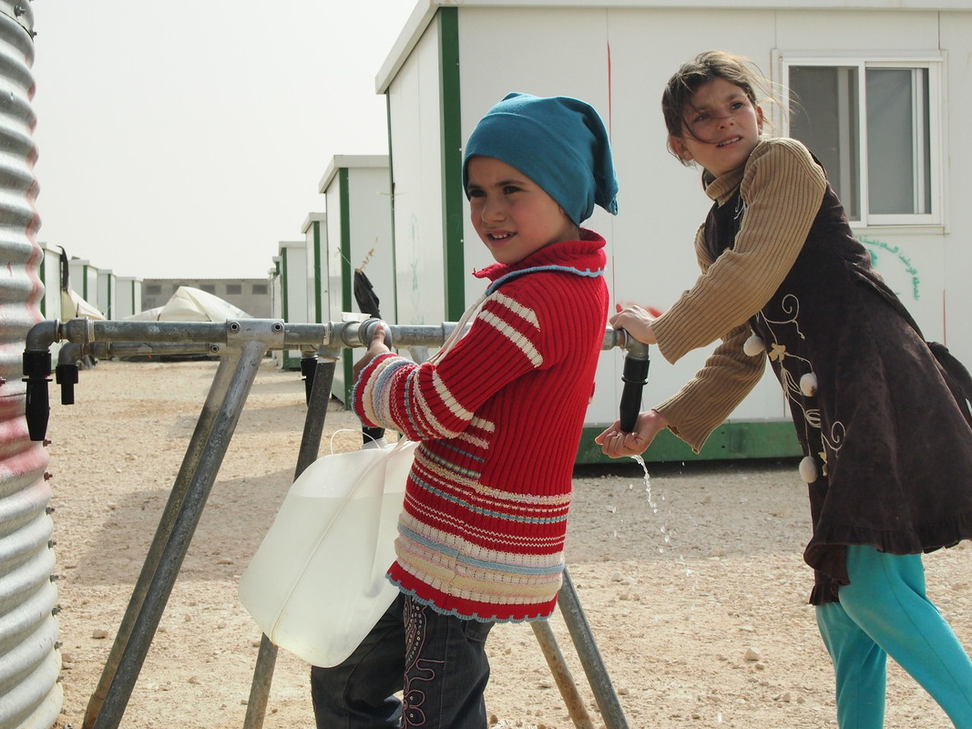Girls collect water from a tap in Zaatari camp, Jordan. Photo: Caroline Gluck/Oxfam