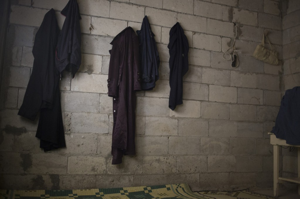 The few belongings that Shatha's family managed to take with them after their home in Syria was destroyed by an air strike hang on bare walls inside the partially constructed building that is serving as their home. Photo: Sam Tarling/Oxfam