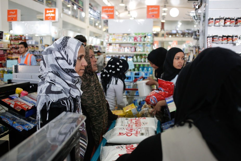 Young Syrians and their Lebanese host visit a grocery store to purchase food and hygiene items with $150 coupons they received from an Oxfam partner organization. Photo: Sam Tarling/Oxfam