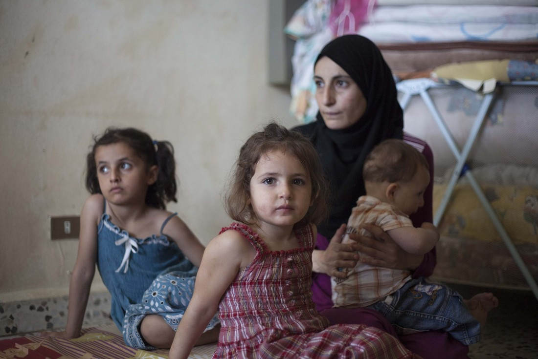 Maysa Abdel Razaq al Akhras and her children sit in the dilapidated apartment that is now their home in Lebanon. Photo by Sam Tarling/Oxfam