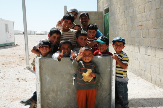 Syrian children pose for a photo next to a newly installed Oxfam water tap in Zaatari Camp, Jordan. Photo: Karl Schembri/Oxfam